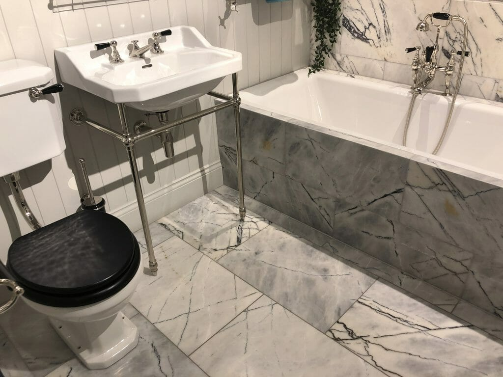 Stock Photo of luxury bathroom suite with white / grey marble wall and floor tiles, white ceramic bath, sink, WC toilet, washroom with stainless steel Victorian mixer tap and shower plumbing, artificial trailing plants, mirrors, towel rail, tiled floor flooring