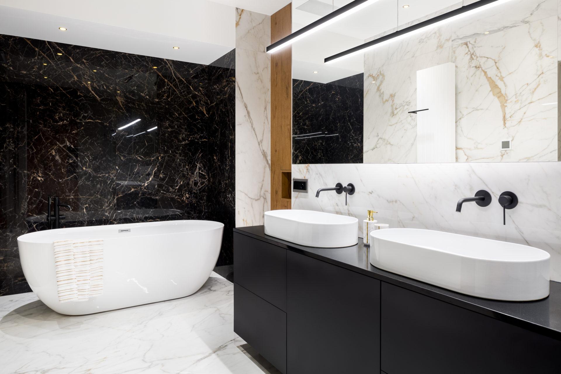 Luxury bathroom with dark and bright marble tiles and big bathtub