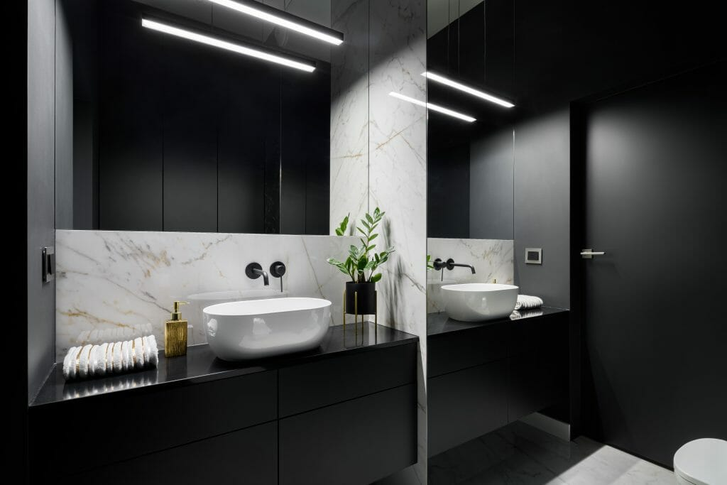 Elegant black bathroom with mirror wall and decorative marble tiles