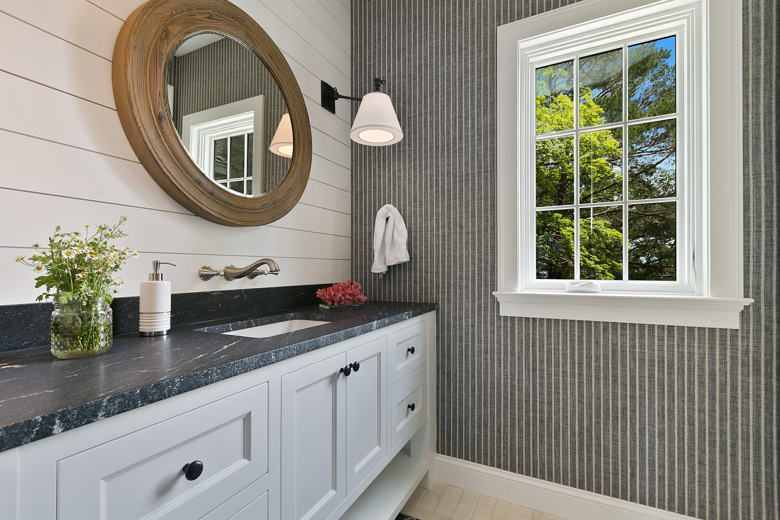 Round mirror and sconce lights on a shiplap wall in bathroom