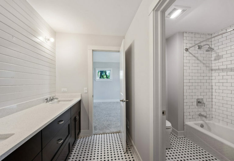 Shiplap walls and black and white tile in new bathroom